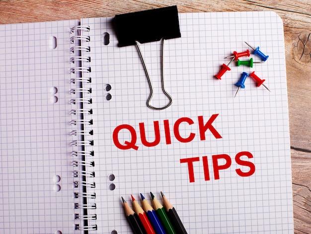 De woorden quick tips zijn geschreven in een notitieboekje in de buurt van veelkleurige potloden en knoppen op een houten oppervlak