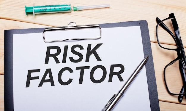 De woorden risicofactor staan op een wit vel papier naast een bril met een zwarte rand, een pen en een spuit. medisch concept