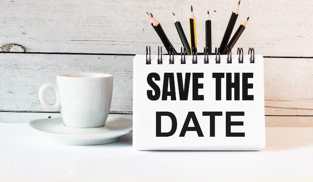 De woorden save the date zijn geschreven in een wit notitieblok naast een witte kop koffie op een licht oppervlak