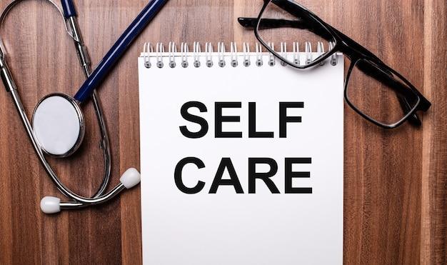 De woorden self care zijn geschreven op wit papier op een houten achtergrond naast een stethoscoop en een bril met zwart montuur. medisch concept