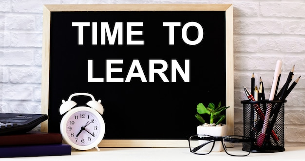 De woorden tijd om te leren staan op het bord naast de witte wekker, glazen, potplant en potloden in een standaard