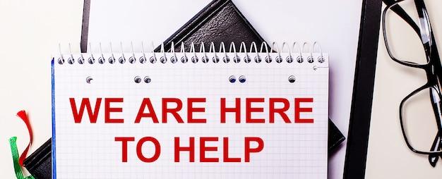 De woorden wij zijn hier om te helpen, zijn in het rood geschreven in een wit notitieboekje naast een bril met een zwart montuur