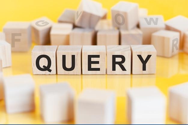 De woordquery is geschreven op een houten kubusstructuur. blokken op een lichte achtergrond. financieel begrip. selectieve focus