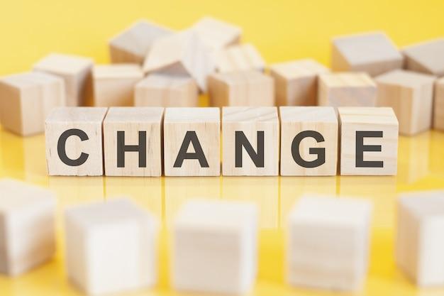 De woordverandering is geschreven op een houten kubusstructuur. blokken op een felgele achtergrond. kan worden gebruikt voor zaken, onderwijs, financieel concept. selectieve aandacht.