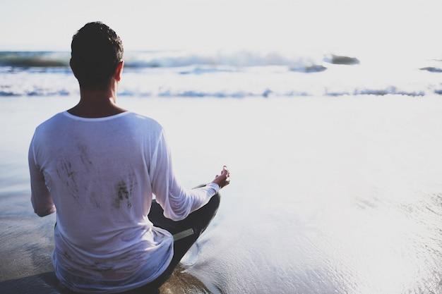 De yoga van de jonge mensenpraktijk op het strand bij zonsondergang.