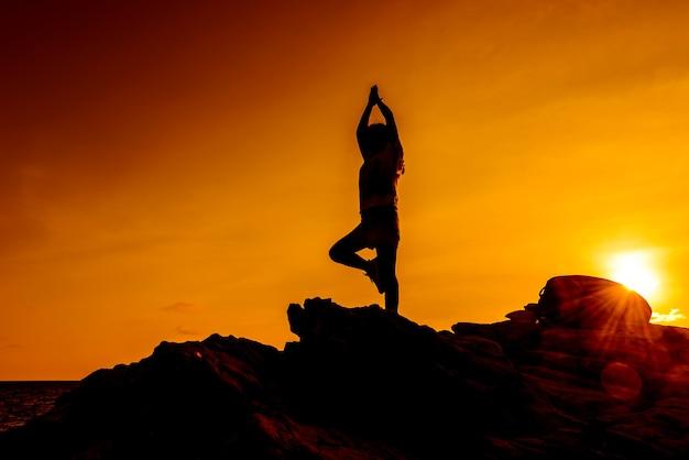 De yoga van de silhouetvrouw op de bergzonsondergang. sporten en een gezonde levensstijl.