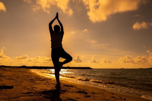 De yoga van de silhouetvrouw op de strandzonsondergang. sporten en een gezonde levensstijl. frisse start van de dag en recreatie.