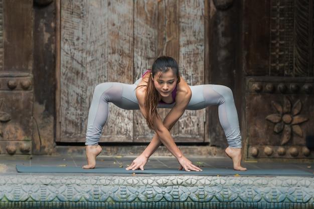 De yogavrouw die oefening met yoga doen stelt thuis.