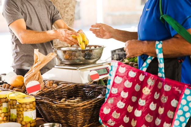 De zak van de mensenholding het kopen bananen van fruitverkoper in markt