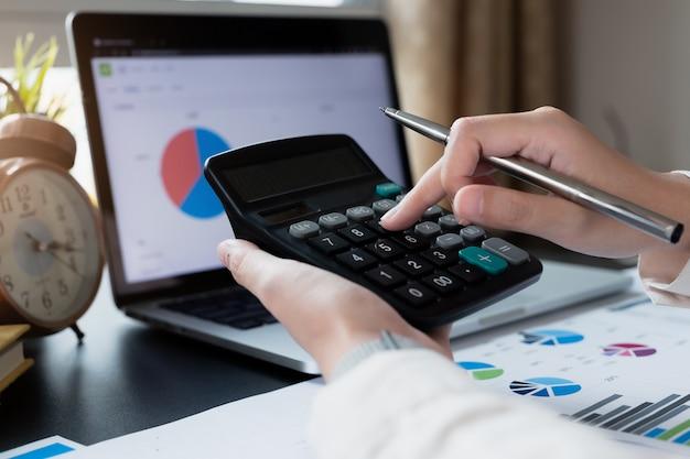 De zaken die calculator en laptop gebruiken voor doen wiskunde financieren op houten bureau op bureau en bedrijfs werkende achtergrond.