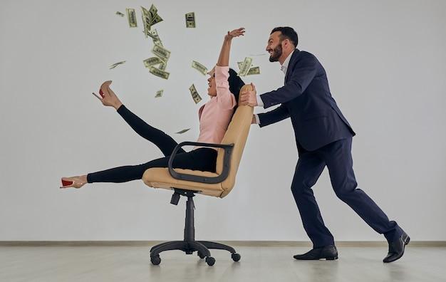 De zaken man en vrouw spelen met stoel