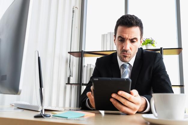 De zakenbaas benadrukt de zakelijke transacties terwijl hij naar de computertablet kijkt.