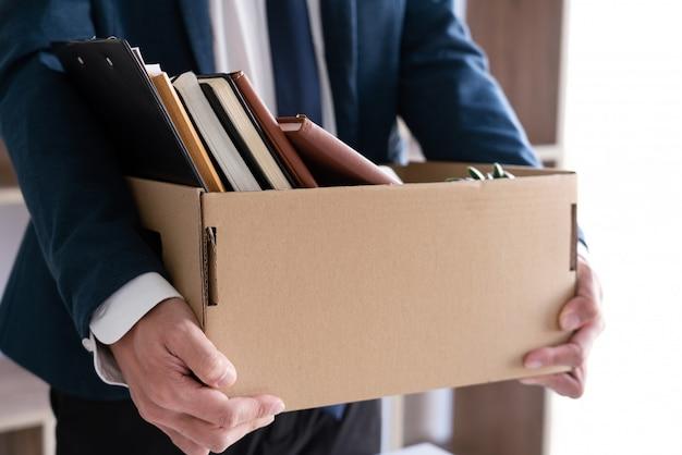 De zakenlieden houden ontslagdocument en verpakken persoonlijk bedrijf op het bruine veranderende werk van de kartondoos, treden concept op