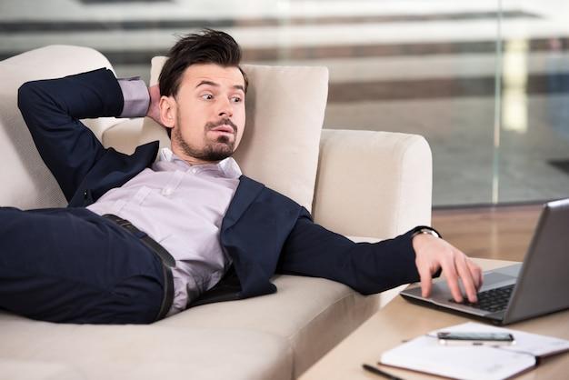 De zakenman bekijkt zijn laptop terwijl het liggen.