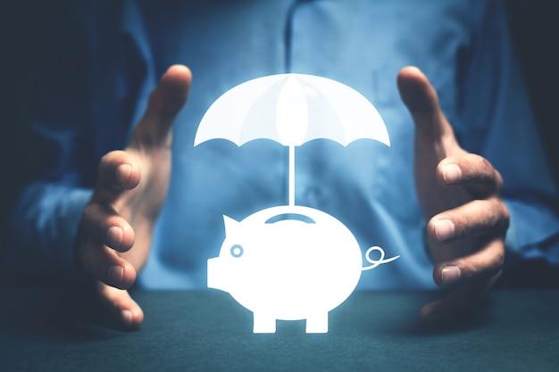 De zakenman beschermt spaarvarken met paraplu. geld besparen. financiële verzekering