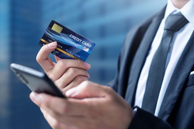 De zakenman betaalt of winkelt door creditcard met smartphone