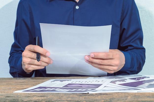 De zakenman controleert de rekeningen en documenten op tafel
