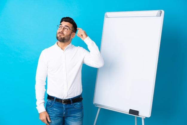 De zakenman die een presentatie op whiteboard geven die een presentatie op whiteboard geven en twijfels hebben met verwart gezichtsuitdrukking
