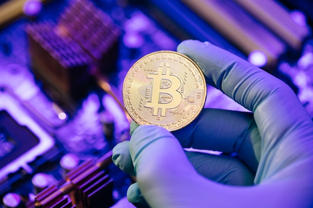 De zakenman dient handschoenen in houdt gouden bitcoin op moederbord