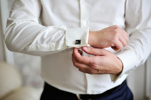 De zakenman draagt een overhemd en manchetknopen in bureau