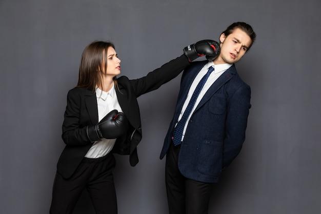 De zakenman en de bedrijfsvrouw van de portretstrijd met kneuzingen op haar wapenslag met geïsoleerde bokshandschoenen