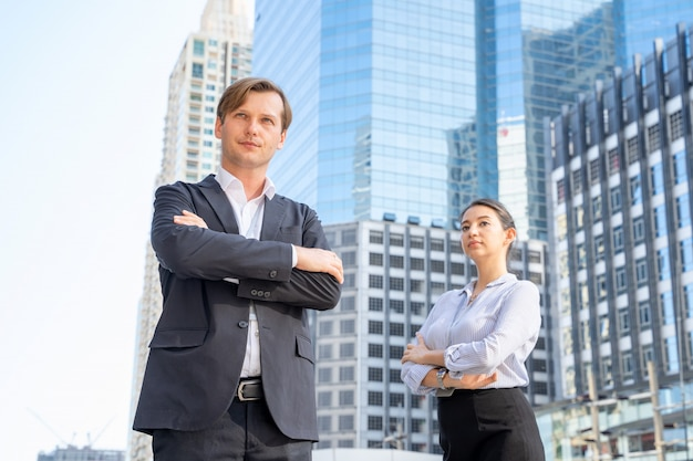 De zakenman en de onderneemster die zich in straat bij de stad bevinden en contacteren het openluchtwerk over bedrijfsprojecten, concept de behendigheid van het werk.
