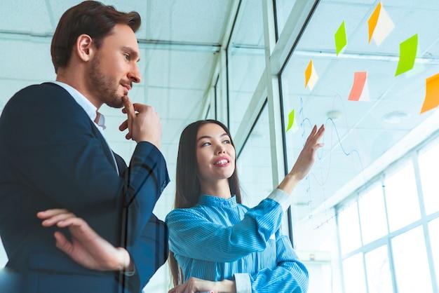 De zakenman en een zakenvrouw bespreken in de buurt van het glas met een grafiek
