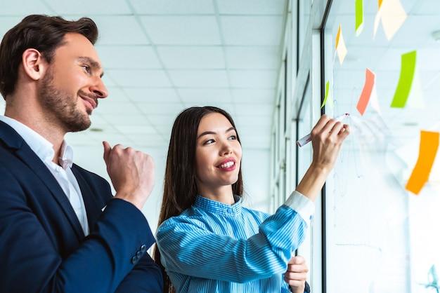 De zakenman en een zakenvrouw die op het kantoorglas tekenen