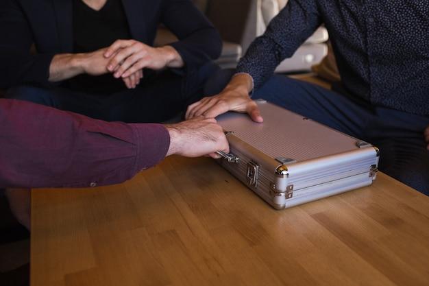 De zakenman geeft de zaak met geld door aan een andere persoon in aanwezigheid van getuigen.