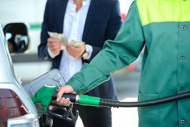 De zakenman geeft geldautomaten, gevulde auto op benzinestation