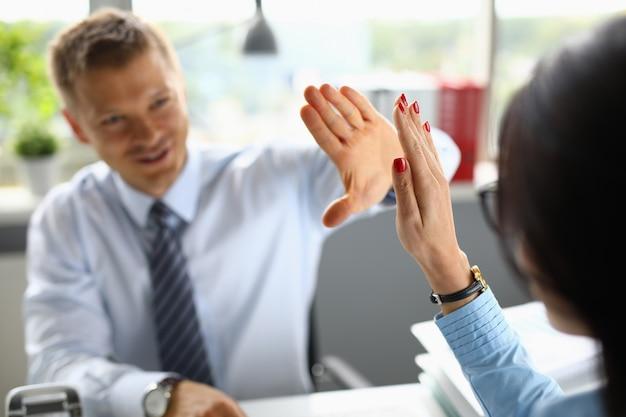 De zakenman glimlacht en begroet zijn collegaclose-up