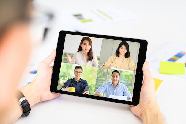 De zakenman heeft een vergadering met asain-collega's over plan in videoconferentie via tablet