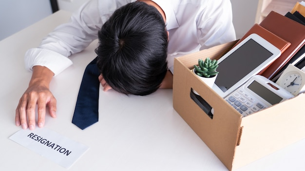 De zakenman heeft spanning om af te treden en de brief van het annuleringscontract, verandering van baanwerkloosheid of ontslagconcept te ondertekenen