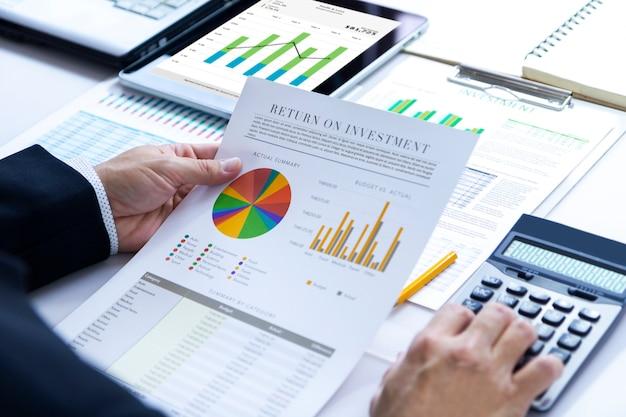 De zakenman herziet diepgaand een financieel rapport voor een rendement op investering of analyse van investeringsrisico's.