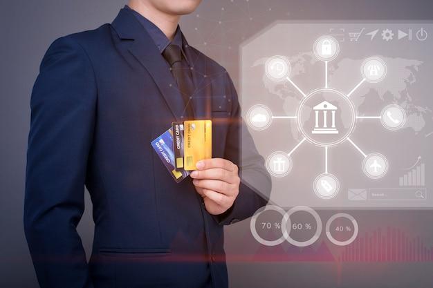 De zakenman houdt creditcard en analyseert financiële bankgegevens over het digitale virtuele scherm