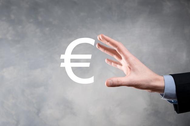 De zakenman houdt de pictogrammen van het geldmuntstuk eur of euro op donkere toonachtergrond. het kweken van geldconcept voor bedrijfsinvesteringen en financiën.