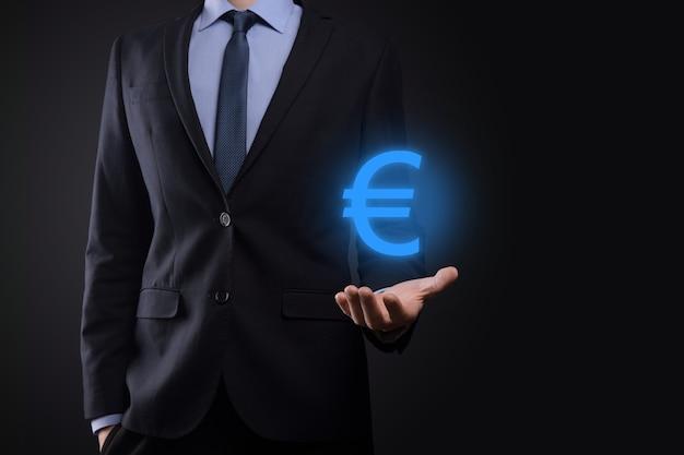 De zakenman houdt de pictogrammen van het geldmuntstuk eur of euro op donkere toonachtergrond.
