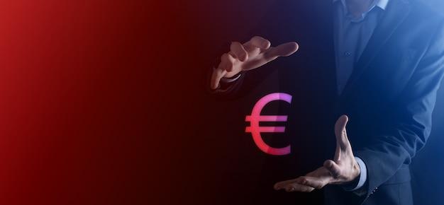 De zakenman houdt de pictogrammen van het geldmuntstuk eur of euro op donkere toonachtergrond