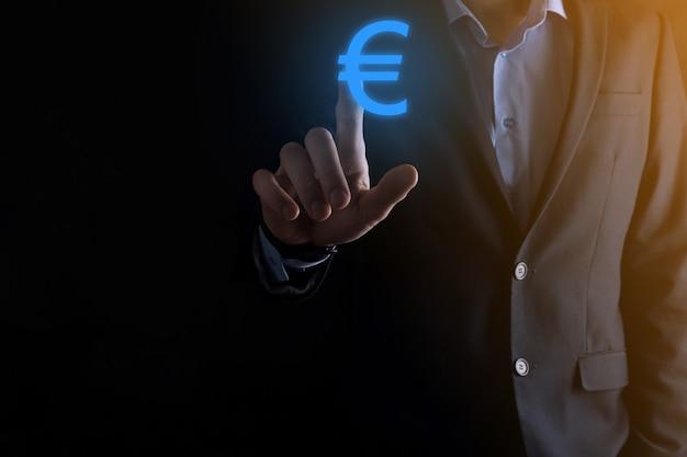 De zakenman houdt de pictogrammen van het geldmuntstuk eur of euro op donkere toonmuur... groeiend geldconcept voor bedrijfsinvesteringen en financiën.