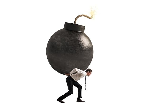De zakenman houdt een bomconcept van moeilijke carrière en mislukking die op wit oppervlak wordt geïsoleerd
