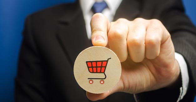 De zakenman houdt een houten blok met het beeld van een supermarktkar - boodschappenwagentje.