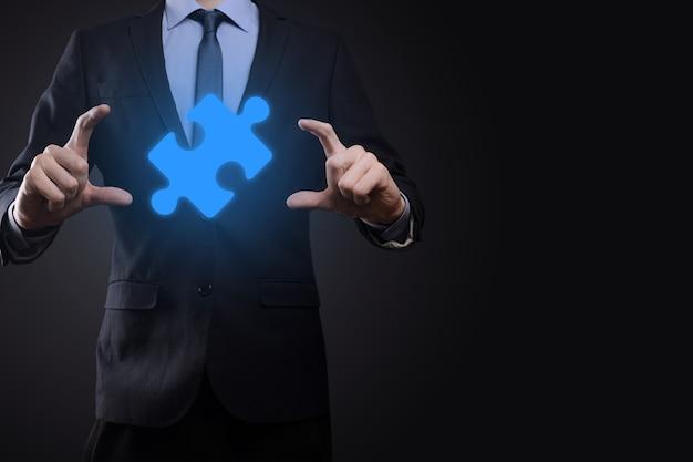 De zakenman houdt een puzzelstukje in zijn handen.