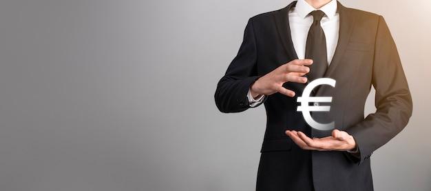 De zakenman houdt geldmuntpictogrammen eur of euro op donkere toonachtergrond... groeiend geldconcept voor bedrijfsinvesteringen en financiën