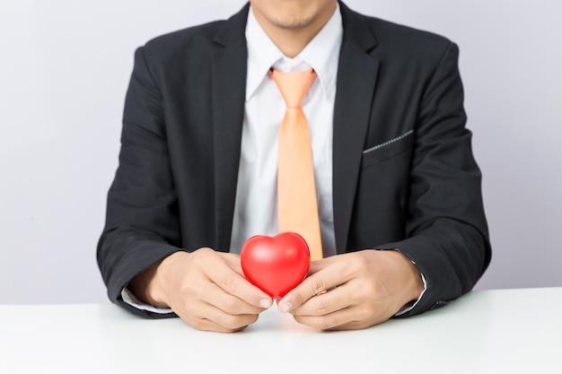 De zakenman houdt het rode hart, geïsoleerde achtergrond stand