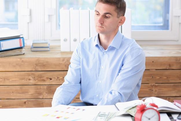 De zakenman in blauw overhemd is verveeld en droevig bij