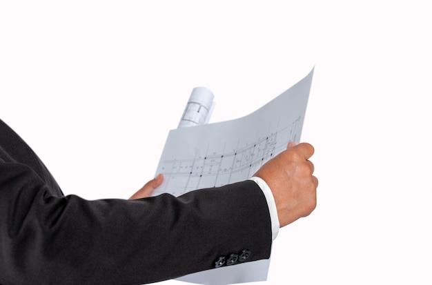 De zakenman in de hand heeft een bouwplan of een architecturaal plan, dat voor verwante professionele onroerende goederen handel, bouw wordt gebruikt.