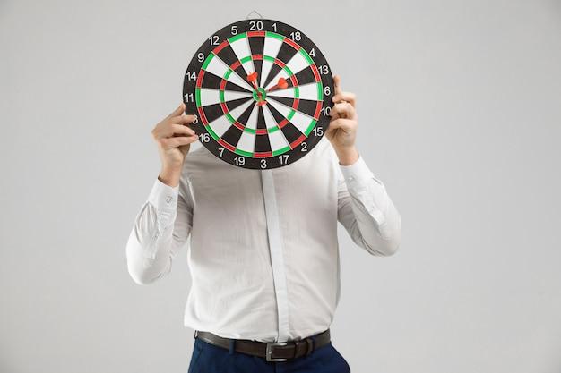 De zakenman in een wit overhemd verborg zijn hoofd achter een doel met pijltjes in centrum op een wit