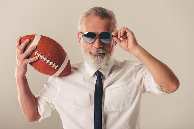 De zakenman in glazen houdt een voetbalbal