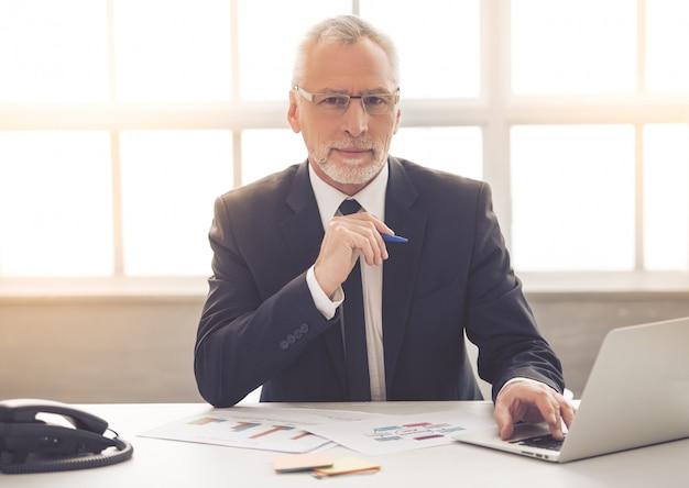 De zakenman in klassiek kostuum en oogglazen gebruikt laptop