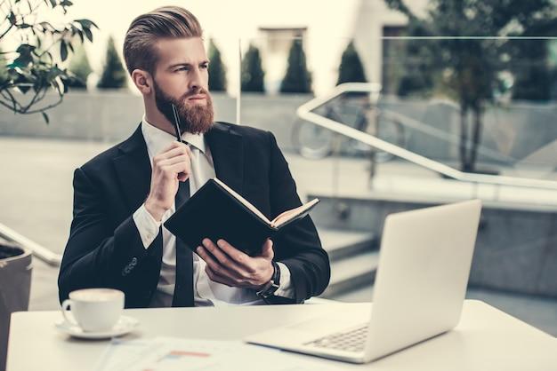 De zakenman in klassiek kostuum gebruikt laptop.